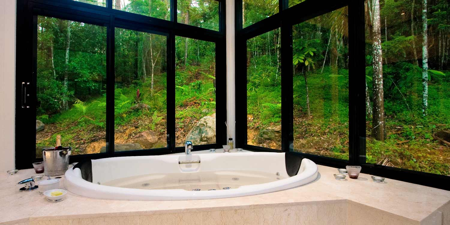 The sunken double spa bath of Cedar Lodge has views to the cool rainforest surrounds