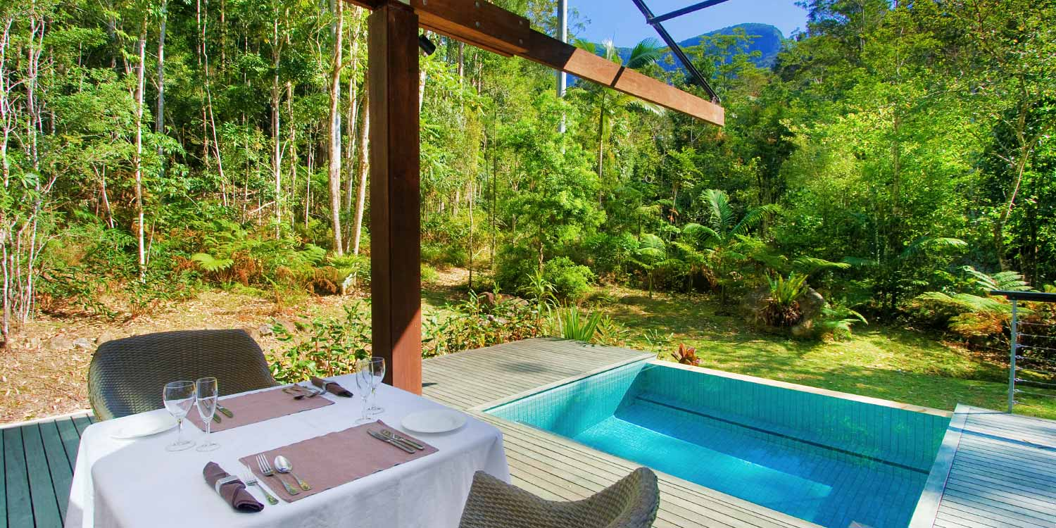 The expansive private deck of the Luxury Rainforest Lodge has views to the rainforest and Mount Springbrook