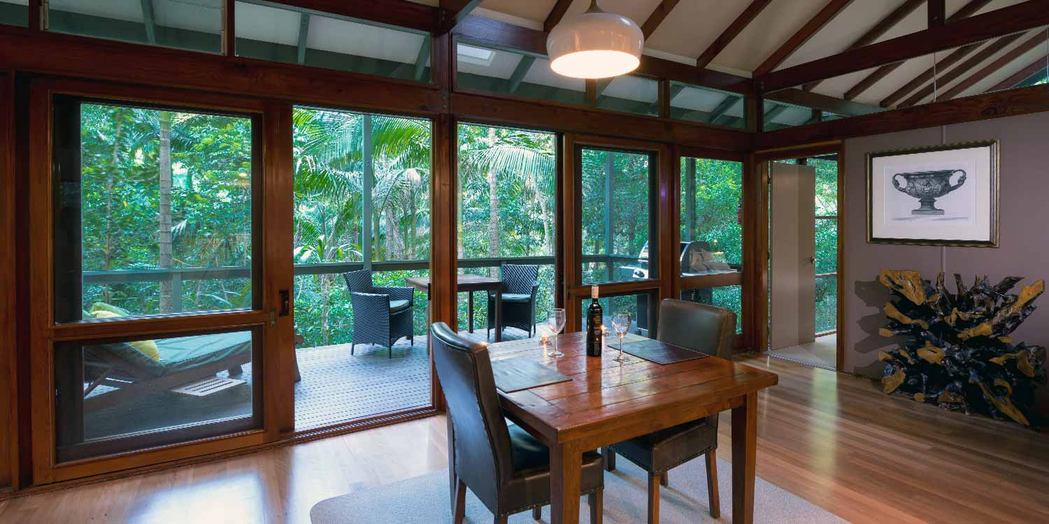 The dining area of the Creekside Spa Cabins have sliding doors that open up to the private deck and rainforest views
