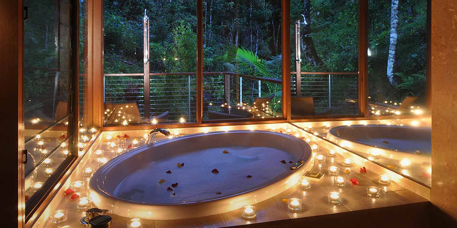 Dozens of candles around a double spa bath at Crystal Creek Rainforest Retreat – the ideal romantic escape for honeymoons or just to get away