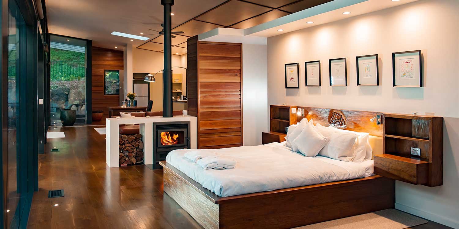 The double sided fireplace in the Luxury Mountain View Lodges warms both bed and living areas, in the hinterland of Byron Bay, New South Wales
