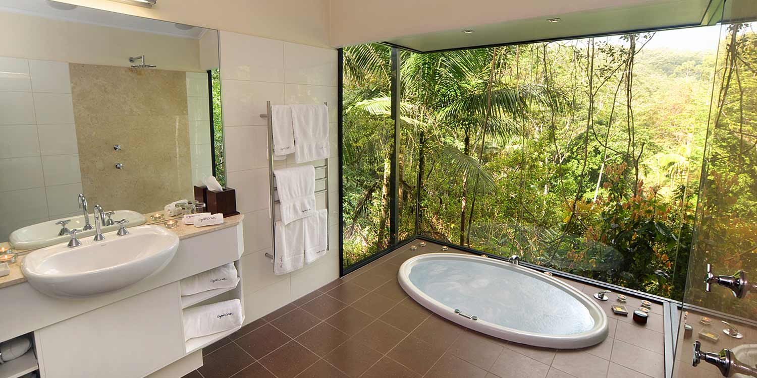 The spacious bathrooms of the Rainforest Canopy Bungalows have double spa baths immersed in a rainforest view